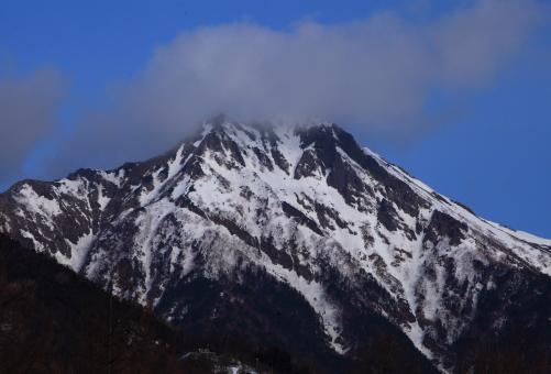 山頂に雲まとう残雪の赤岳