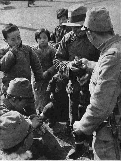 19371227敵前上陸以来激戦また猛闘、快速また追撃、夜に日をついでの戦と進撃に、華やかな南京入りをした快速部隊の兵隊さん達、ひなたぼっこをしながら速製の支那語に、手まね、足まねを加えて支那良民や子供と話を