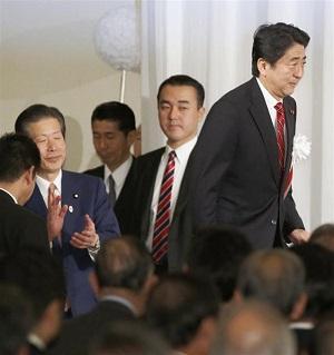 首会談後、公明党結党50周年の記念パーティーで登壇する安倍首相。左は同党の山口代表=11月17日夜、東京都内のホテル