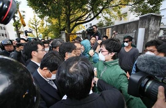 京都大学熊野寮へ捜査に入る警察関係者らとそれを阻止しようとする学生ら=13日午後2時22分、京都市左京区
