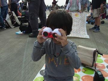 双眼鏡で飛行機を見る息子