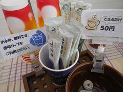[写真]受付ハウス内のコーヒーコーナーの様子(紙コップ、スティクコーヒー、マドラーを並べています)