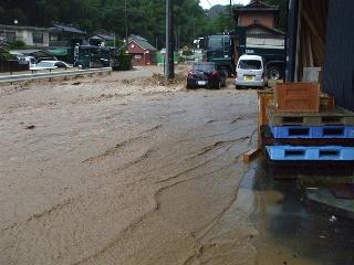 土砂の混じった茶色い水が道路を覆います。