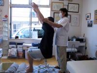 両腕を前から頭上に向かって上げる動作施術前