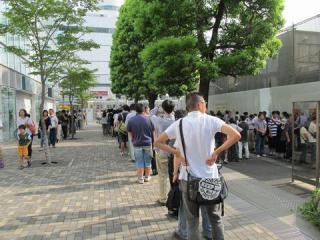 購入待ちの列は調布駅前ロータリー内を飛び出し、駅西側の踏切近くまで延びた。