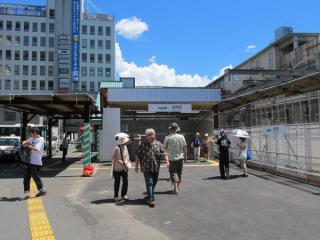 地下化された駅の入口。左後ろに見える緑色の屋根が地上時代の橋上駅舎の入口。