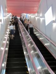 地下1階改札内コンコースからホームへ降りるエスカレータの入口。案内板のカラーは上り線が赤、下り線が青に統一されている。