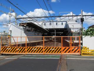 踏切から布田駅の地上ホームを見る。地下化された区間の踏切は全て線路側に工事用のバリケードが設置された。