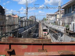 国領駅新宿方の踏切跡から地下に進入する列車を見下ろす。