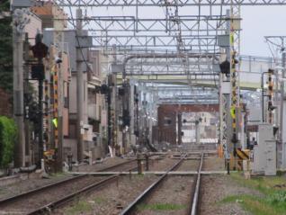 調布駅端の踏切から京王八王子方面を見る。奥に見える茶色い枠が設置されているあたりが地下出口。手前にある陸橋は鶴川街道。