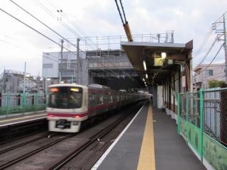 布田駅のホーム上から建設中の新駅舎を見る。