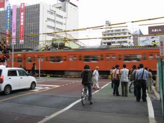武蔵小金井駅東側にあった小金井街道踏切。オレンジ色の201系も高架化とともに消えた。
