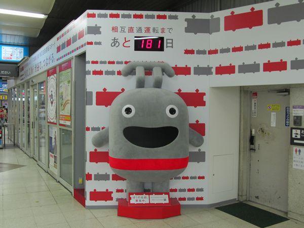 渋谷駅に設置された直通運転のカウントダウンボードと新キャラクターのぬいぐるみ。ぬいぐるみは左側の空間から中に入って口から顔を出すこともでき、お子様たちに人気。