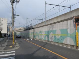 大崎支線の西側を通る道路から大崎支線の盛土高架を見上げる。