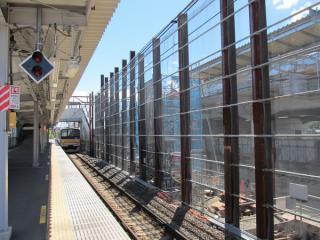稲城長沼駅の地上ホーム。旧下り線ホームは撤去が完了し、高架橋の橋脚建設が進む。跨線橋は階段が上り線側に移設され、短縮された。