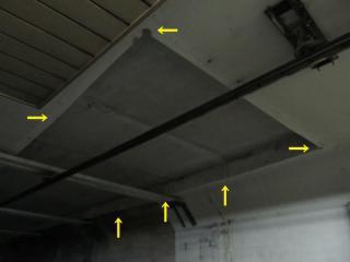 切り取られた天井を拡大。四隅にはコア抜きをした時にできたと思われる丸い断面が見える。(矢印の先)
