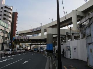 駅前交番の前から第一京浜をまたぐ空港線の高架橋を見る。3階の下り線でも架線柱の設置が始まった。
