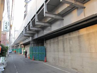 高架下から上り線の仮設高架を見る。桁の下には地上へ降りる旧上り線のよう壁が残っている。