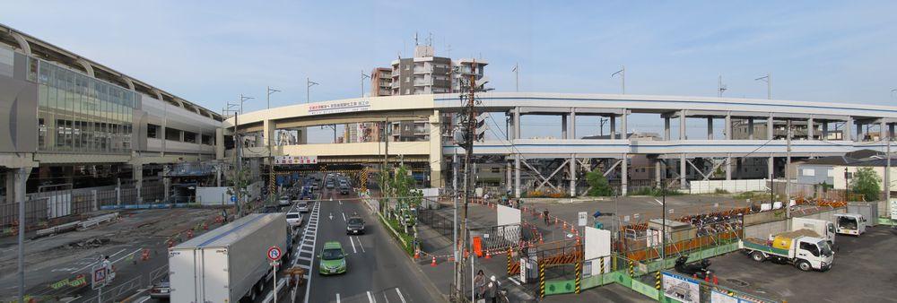 第一京浜をまたぐ新しい歩道橋から第一京浜を見下ろす。右の広い空き地には今後駅前ロータリーが建設される。