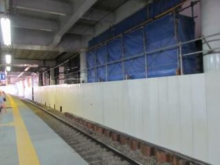 地上の下り線ホームから工事中の高架の下り線ホームへ向かう階段・エスカレータを見る。