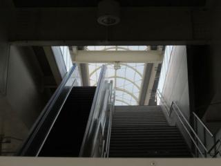 下り線ホームへ向かう階段を見上げる。下り線ホームは中央が膜屋根となっている。