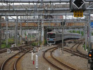 大崎駅ホーム端から地下へ進入していくりんかい線70-000形電車を見る。中央に見える錆びた橋桁は百反歩道橋。その奥では横須賀線・東海道新幹線が直交している。