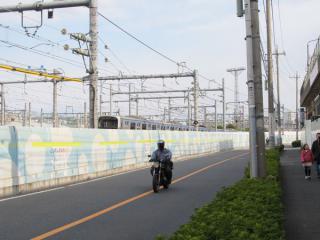大崎支線の脇を通る道路から地下に入るりんかい線の列車を見る。