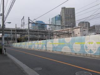 大崎駅入口の架線。右のベージュの建物がJR品川変電所。