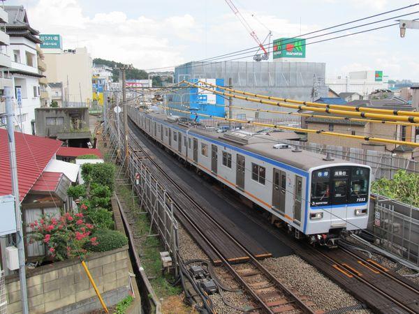 掘削が開始された西谷駅の横浜寄り。相鉄の新しいコーポレートカラーに塗り替えられた新7000系が通過。