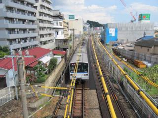 西谷駅横浜方にある歩道橋から横浜方面を見る。線路両脇は土留壁の打ち込み作業が行われている。右奥のネットがかかった建物は新築中の西谷地区センター。
