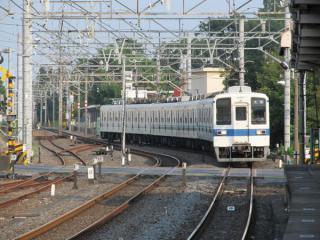 野田市駅のホーム端から梅郷駅方面を見る。電車の先頭車両の手前にあるのが主要地方道野田牛久線の踏切。