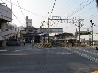 愛宕駅の駅舎とホーム。手前は主要地方道つくば野田線の踏切。