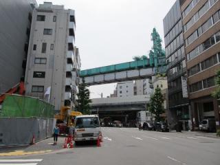 交差する道路から高架橋上に停止中の架設機を見る。