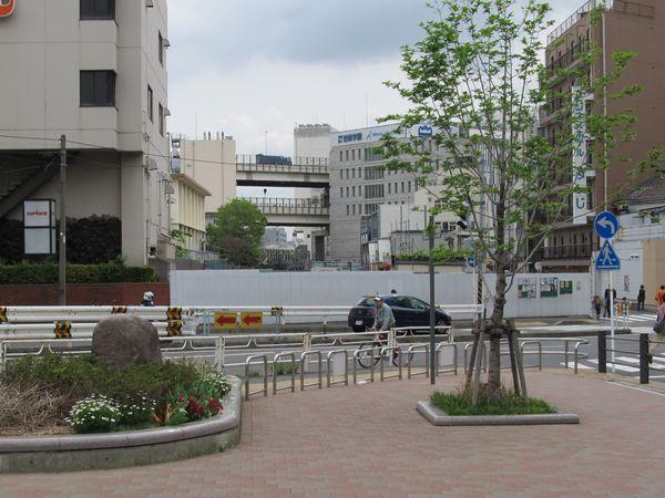 この先は横浜駅西口駅ビル再開発の事業用地となっている。奥の二重高架は首都高速2号三ッ沢線。その下には拡幅された横須賀線ホームを覆う骨組みが見える。