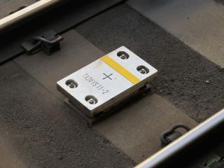 駅構内の線路上に設置されたTASC用地上子。D-ATCの地上子と形状は同じだが、ラベルに「TA」があるため見分けることが可能。