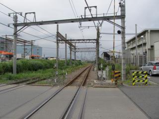 東京貨物ターミナル駅構内へ入る踏切から地下へ入る入出庫線を見る。