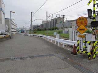 東京貨物ターミナル駅へ向かう踏切から八潮車両基地構内を見る。車両基地入口には保守機材線が設置されており、この日はバキュームカーを載せた貨車がとまっていた。
