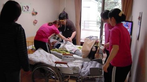 横須賀市西浦賀6丁目の老人ホーム太陽の家の職員の方々が99歳の叔母さんを食堂へ運ぶ為に車椅子ベッドに乗せる光景をデジカメで撮影した