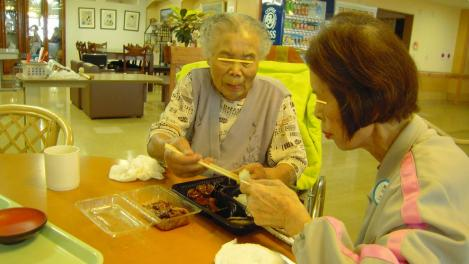 老人ホームで99歳の叔母さんと81歳の母がお互いに焼肉弁当の焼肉を譲り合いながら食べている光景を隣りからデジカメで撮影しました